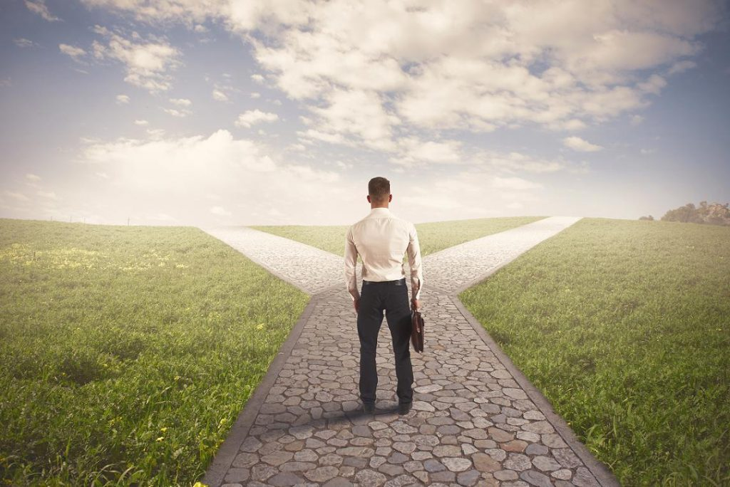 Image of man at a crossroads trying to decide which career option to take