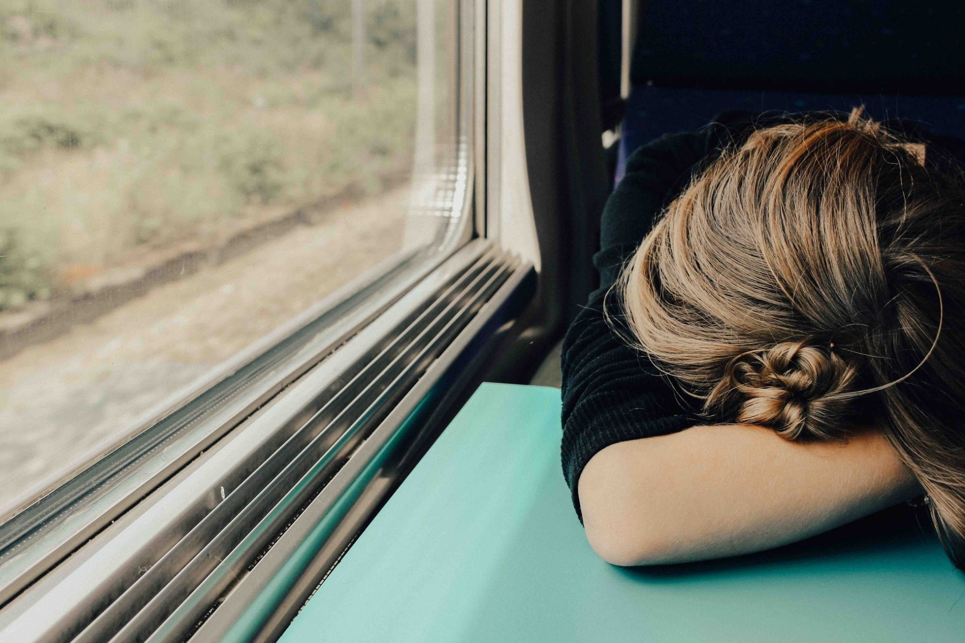 Image of female commuter asleep on train resting her head on the table