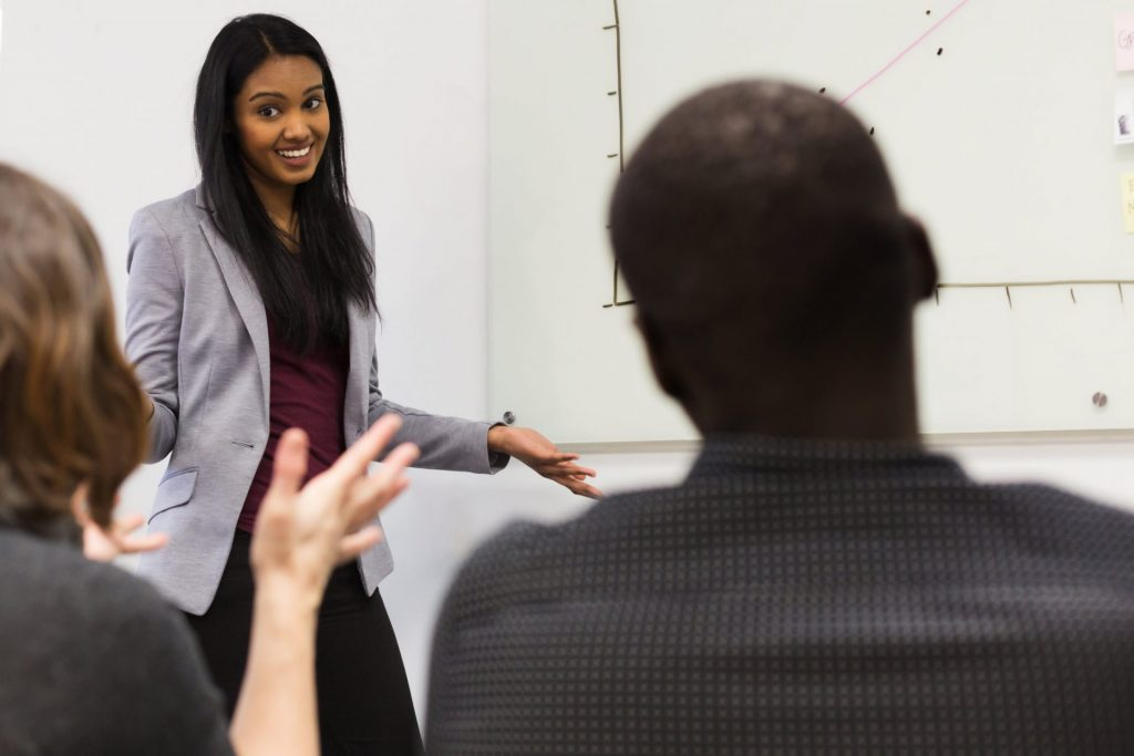 Image of young woman confidently delivering a presentation NLP