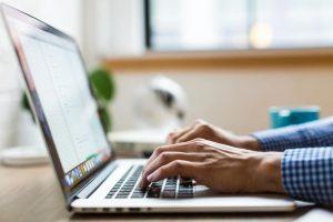 Image of man typing on laptop working on LinkedIn profile